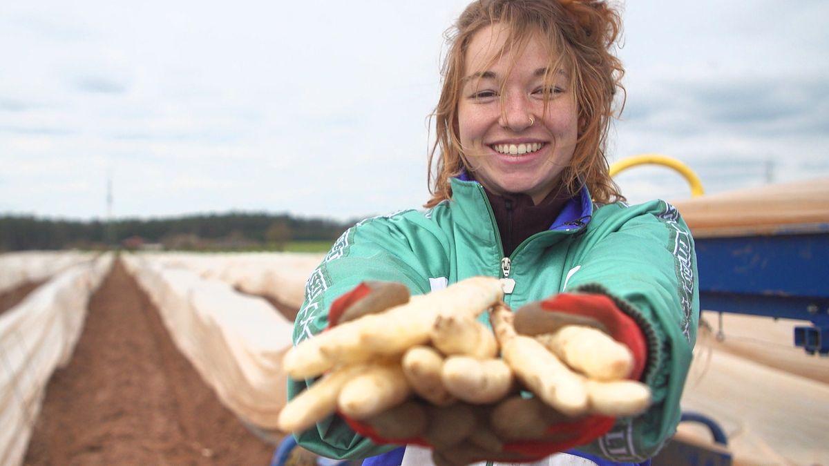 Studentin Johanna Ostermair zeigt stolz ihre ersten selbst geernteten Spargelstangen.