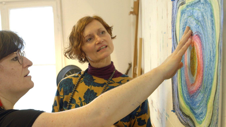 Die Münchner Kunsttherapeutin Doris Seeberger bespricht mit einer Klientin ein Bild