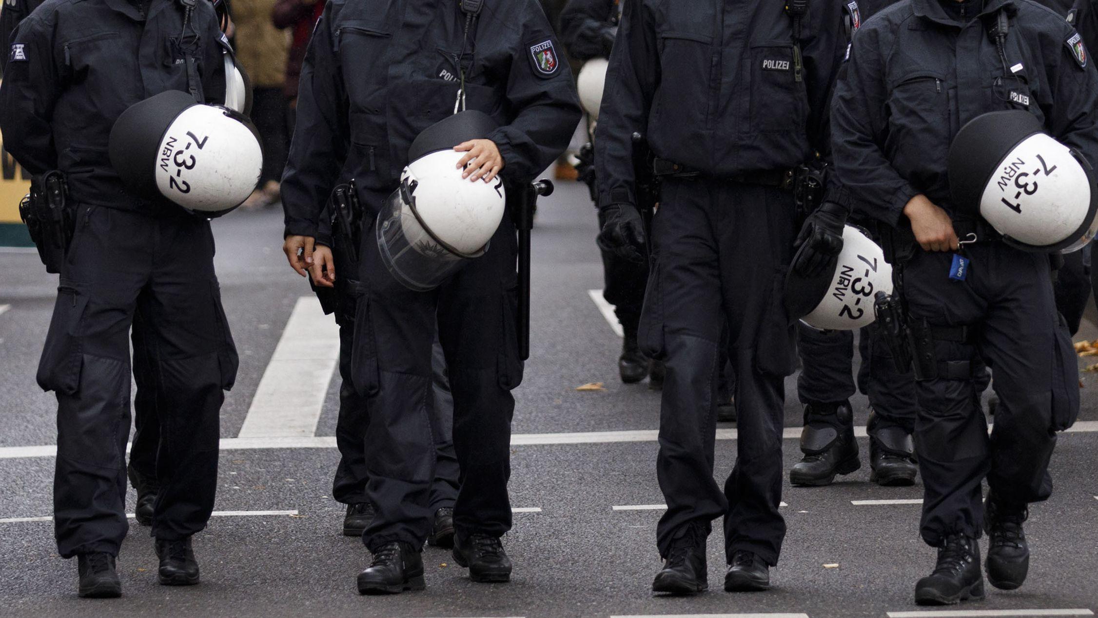 Polizeibeamte gehen vor Demonstranten her (Symbolbild)