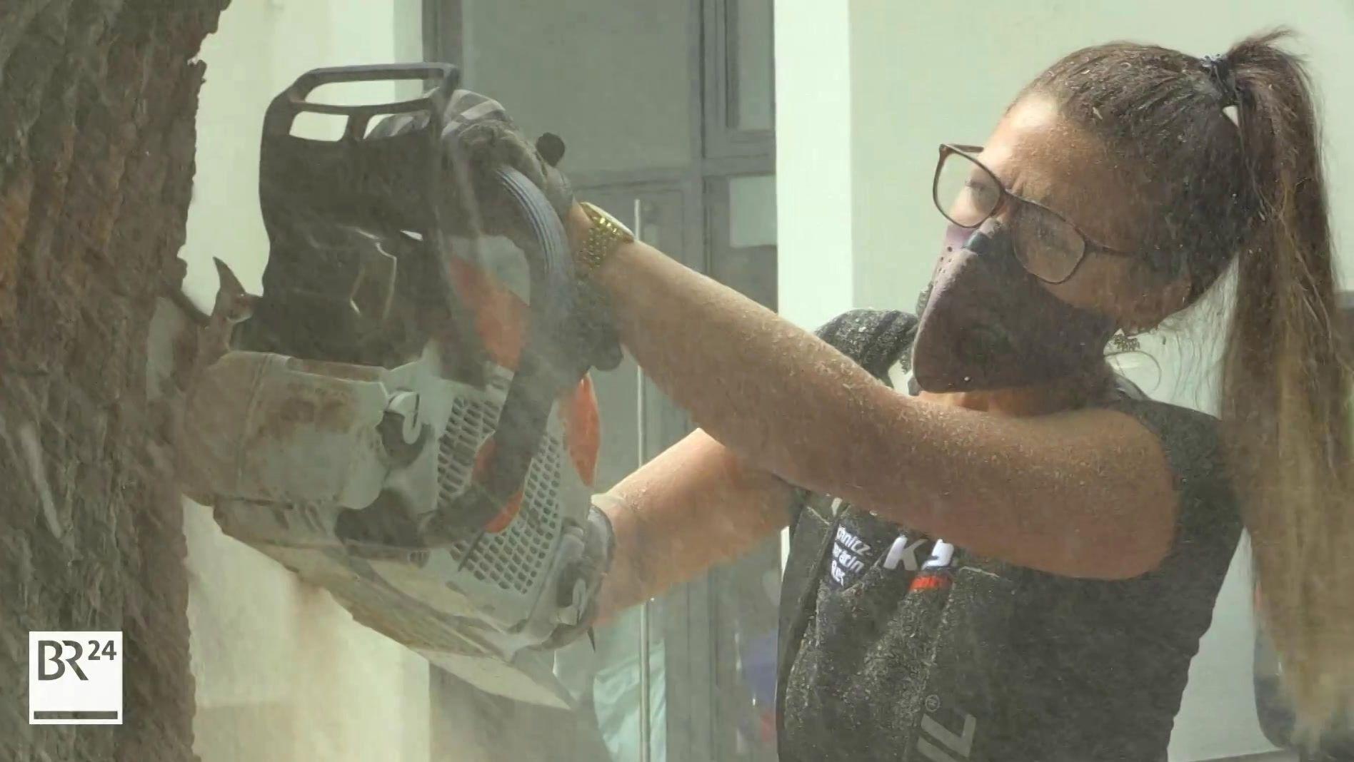 Künstlerin bearbeitet Baumstamm mit der Kettensäge
