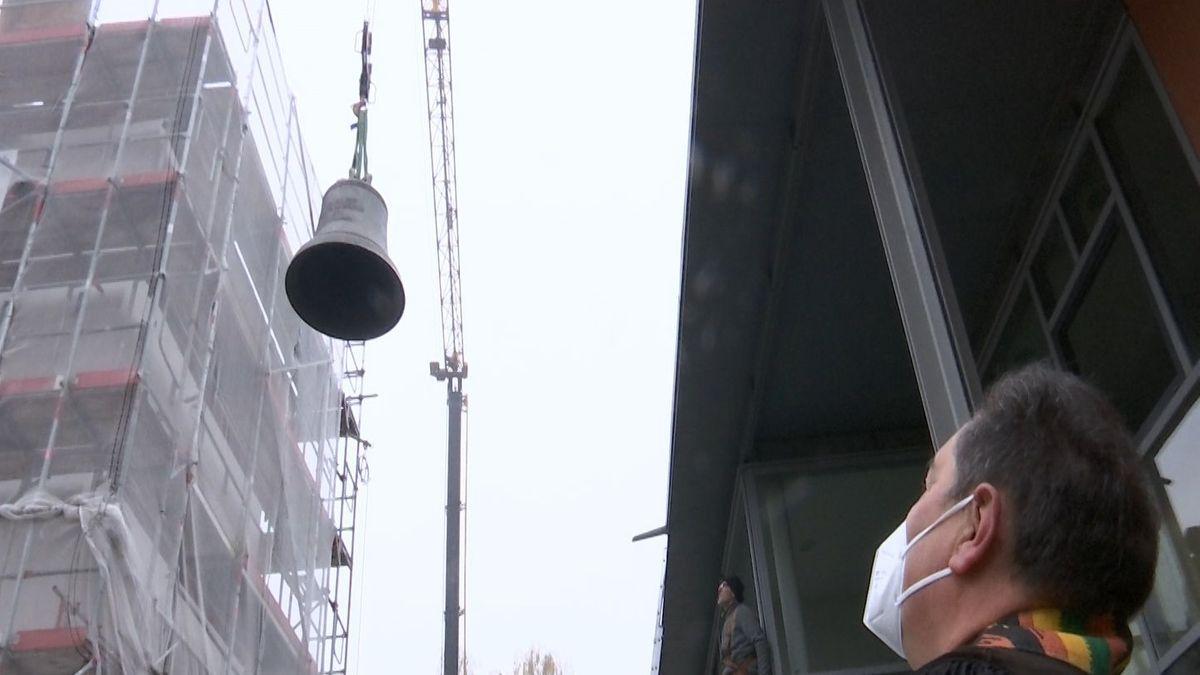 Pfarrer Markus Krusche  beobachtet das Einheben einer Glocke.