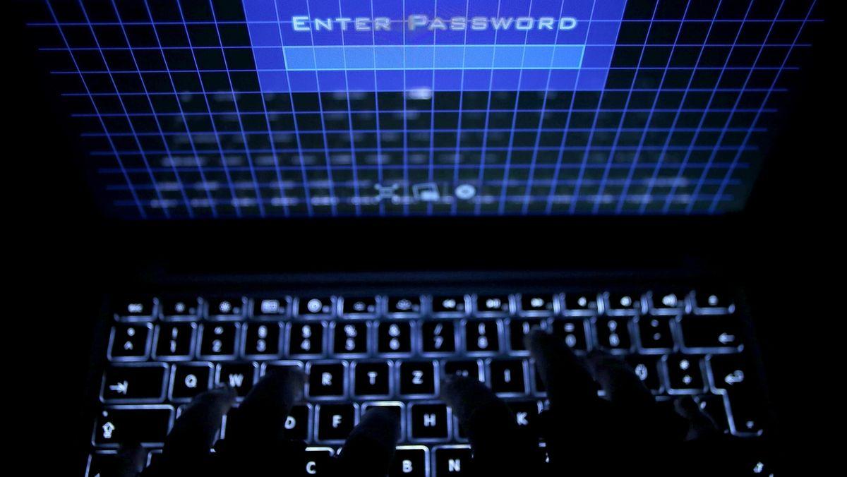 Finger tippen im Dunkeln auf einer erleuchteten PC-Tastatur (Symbolbild)