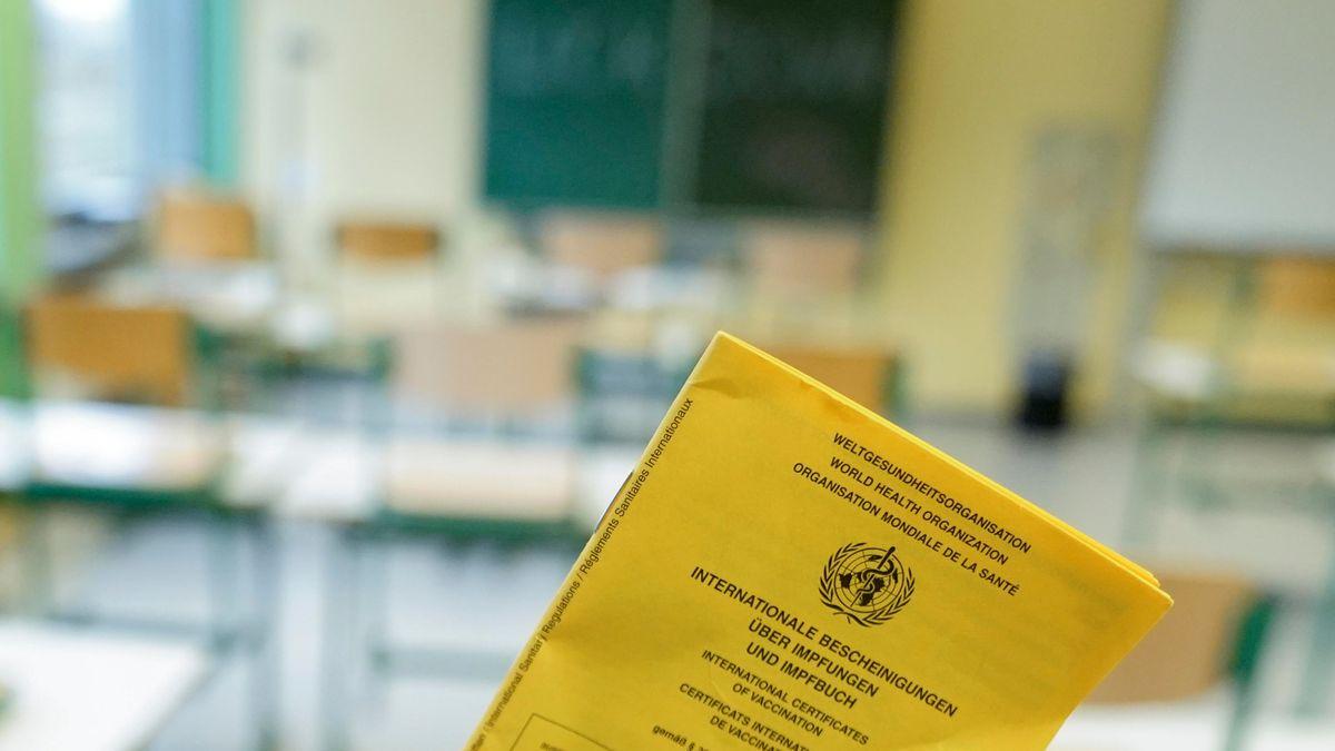 Impfpass vor dem Hintergrund eines Klassenzimmers