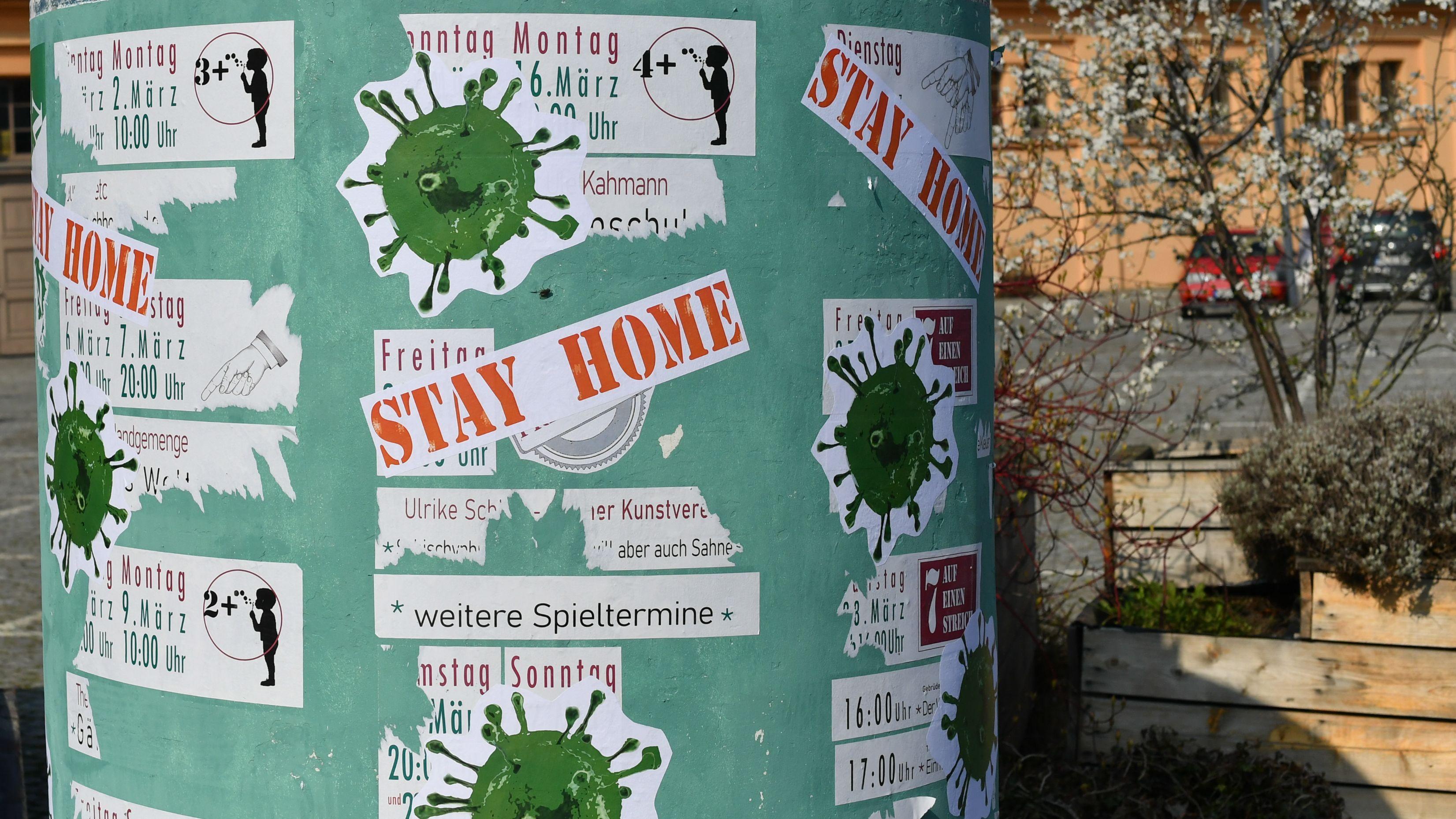 """Litfaßsäule mit Veranstaltungen, die aufgrund von Corona abgesagt wurden. Darüber Aufkleber von stilisiertem Virus und der Aufforderung """"STAY HOME""""."""