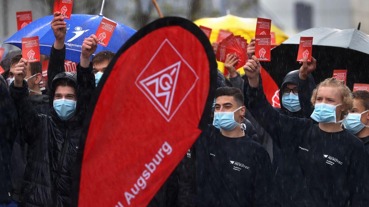 """Mitarbeiter der Airbus-Tochter Premium Aerotec demonstrieren mit symbolischen """"roten Karten"""" auf dem Betriebsgelände des Unternehmens in Augsburg."""