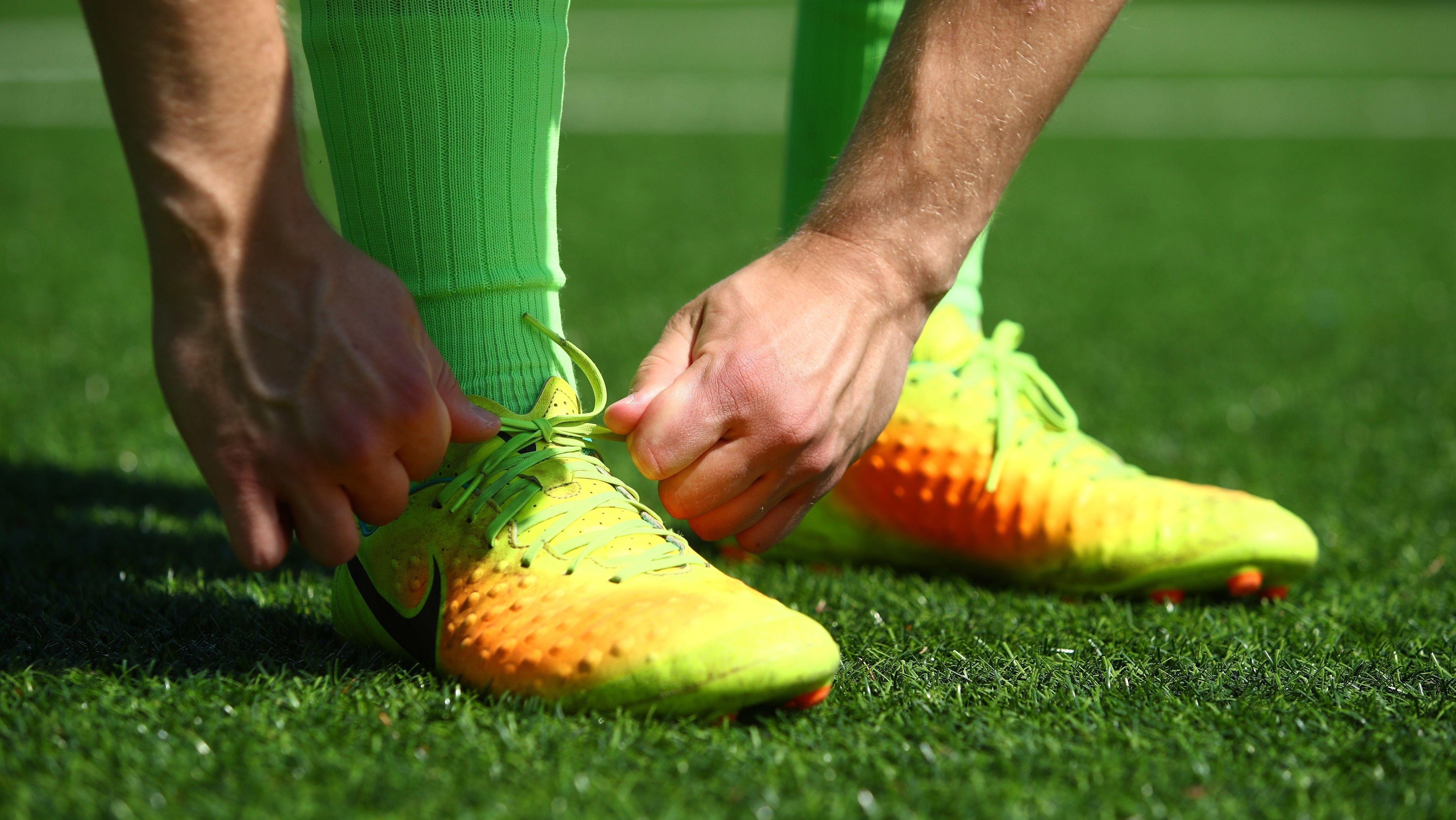 Ein Fußballspieler schnürt sich die Schuhe (Symbolbild).
