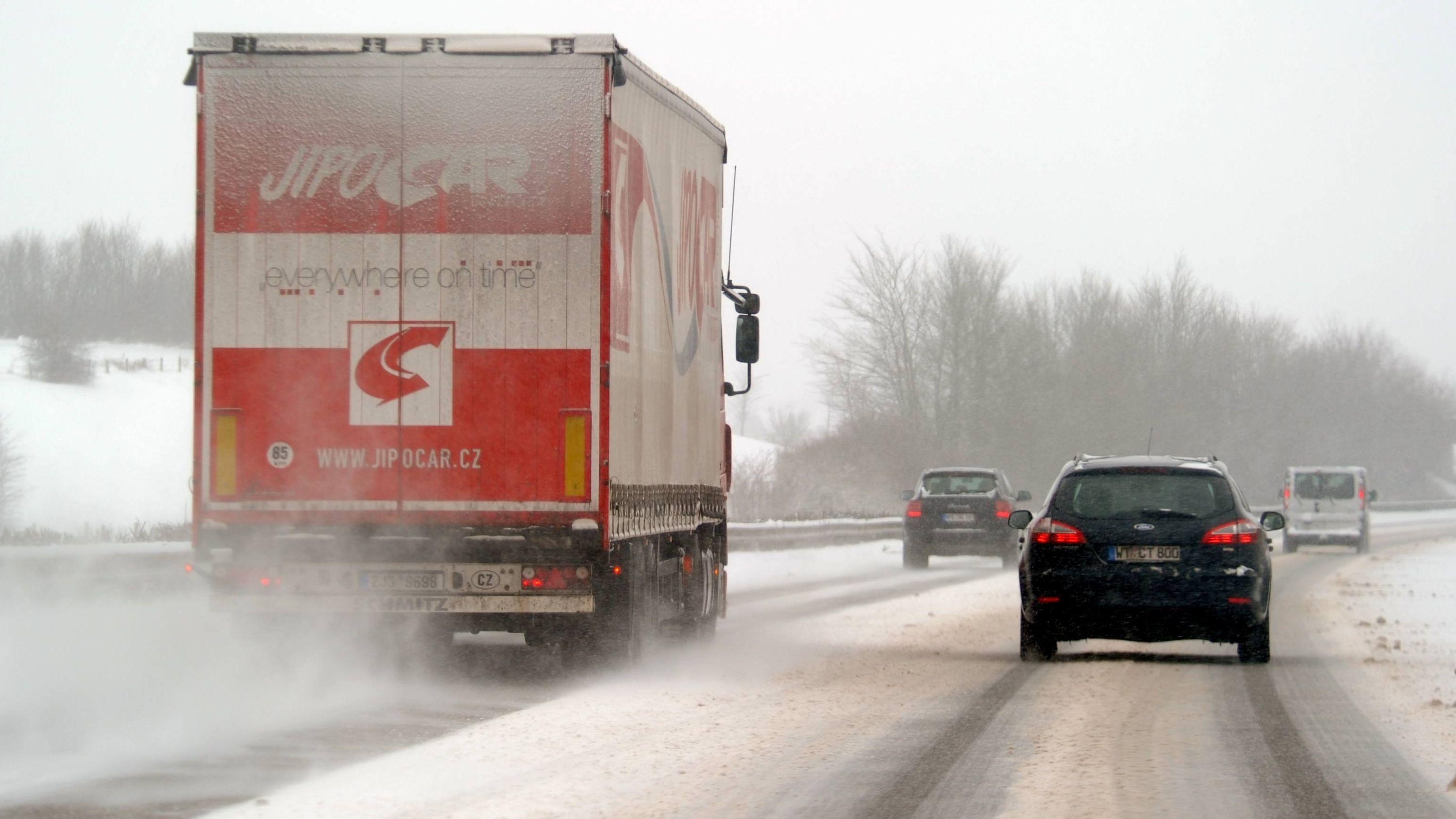 Ein Lkw überholt auf auf der schneeglatten Schnellstraße andere Pkws (Archivbild)