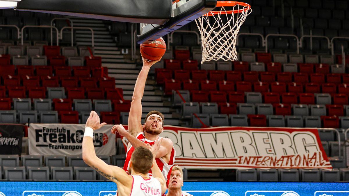 Chase Fieler (Brose Bamberg) kann sich gegen Deividas Gailus und Benjamin Lischka (Telekom Baskets Bonn) durchsetzen.