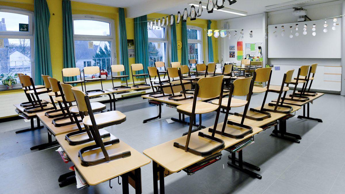 Leeres Klassenzimmer, in dem die Stühle auf den Bänken stehen.
