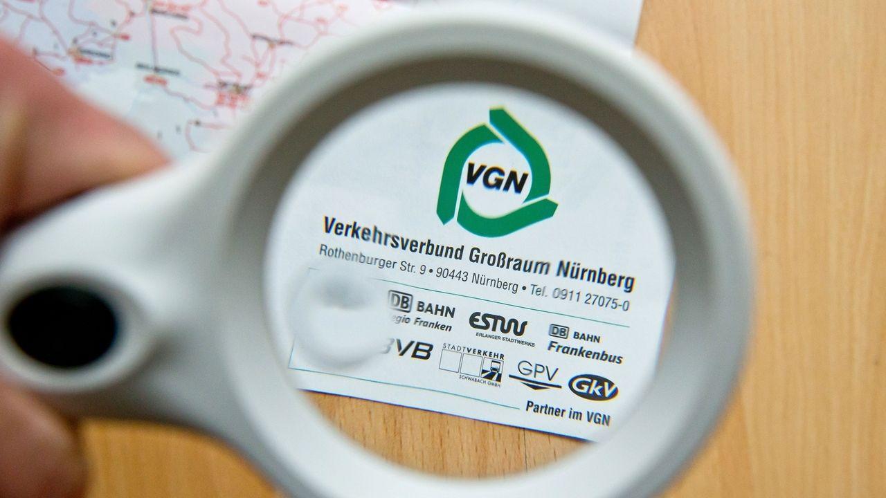 Eine Lupe auf einer Landkarte über dem Logo des Verkehrsverbund für den Großraum Nürnberg (VGN).