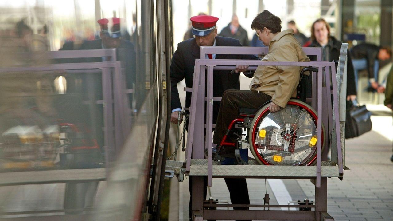 Bahnmitarbeiter hilft Rollstuhlfahrerin mit Hilfe einer Spezialrampe in den Zug