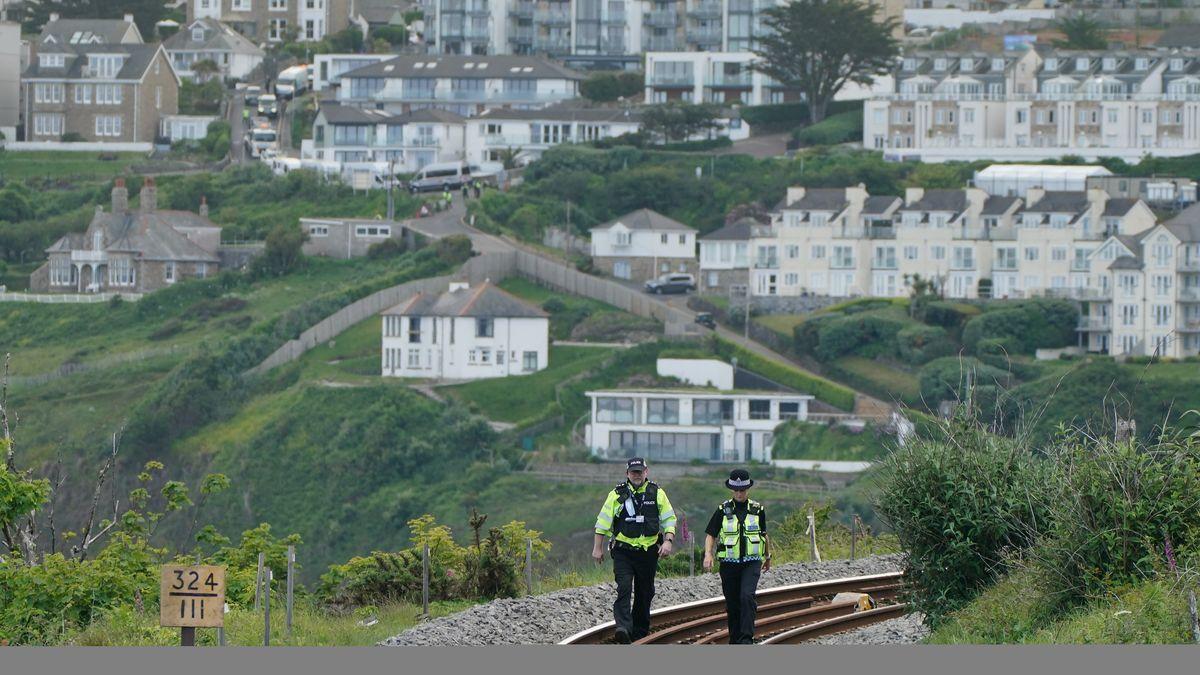 Zwei Polizisten gehen eine Bahnstrecke ab, dahinter Häuser von Carbis Bay