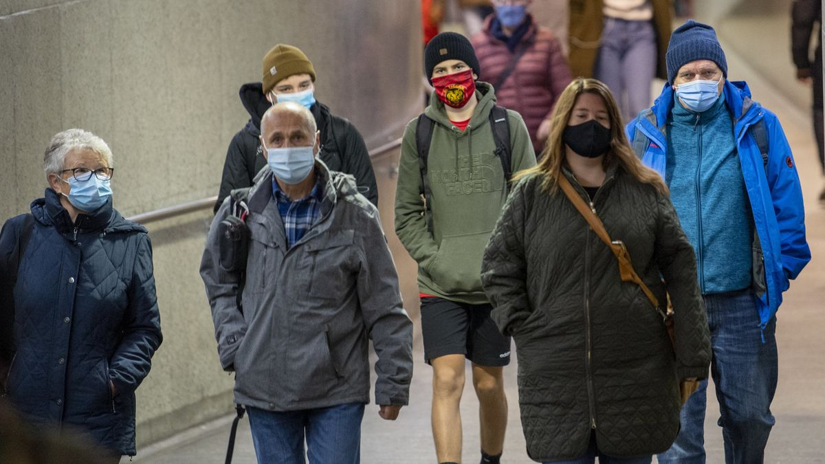 Menschen sind mit Mund-Nasenschutz unterwegs