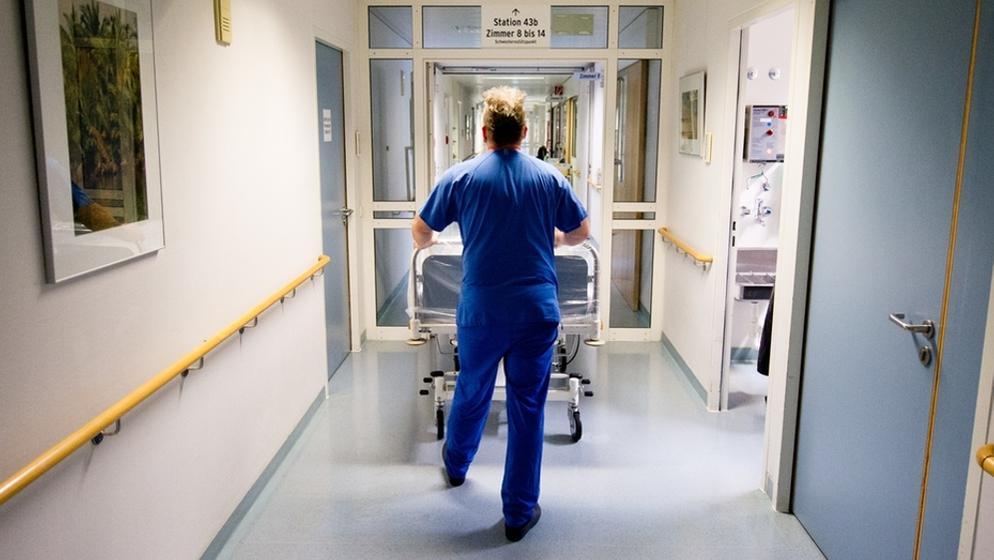 Krankenpfleger schiebt Bett | Bild:picture-alliance/dpa