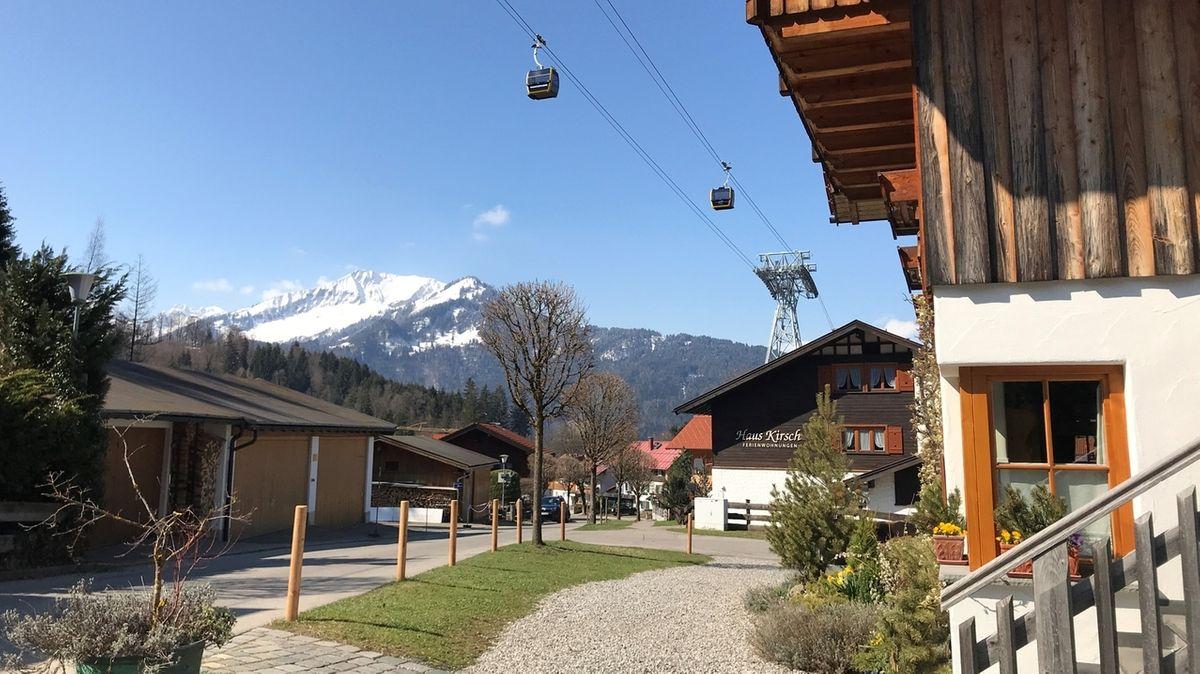 """Blick bei Sonnenschein vor dem """"Haus Kirsch"""" in Oberstdorf von unten auf die Nebelhornbahn."""