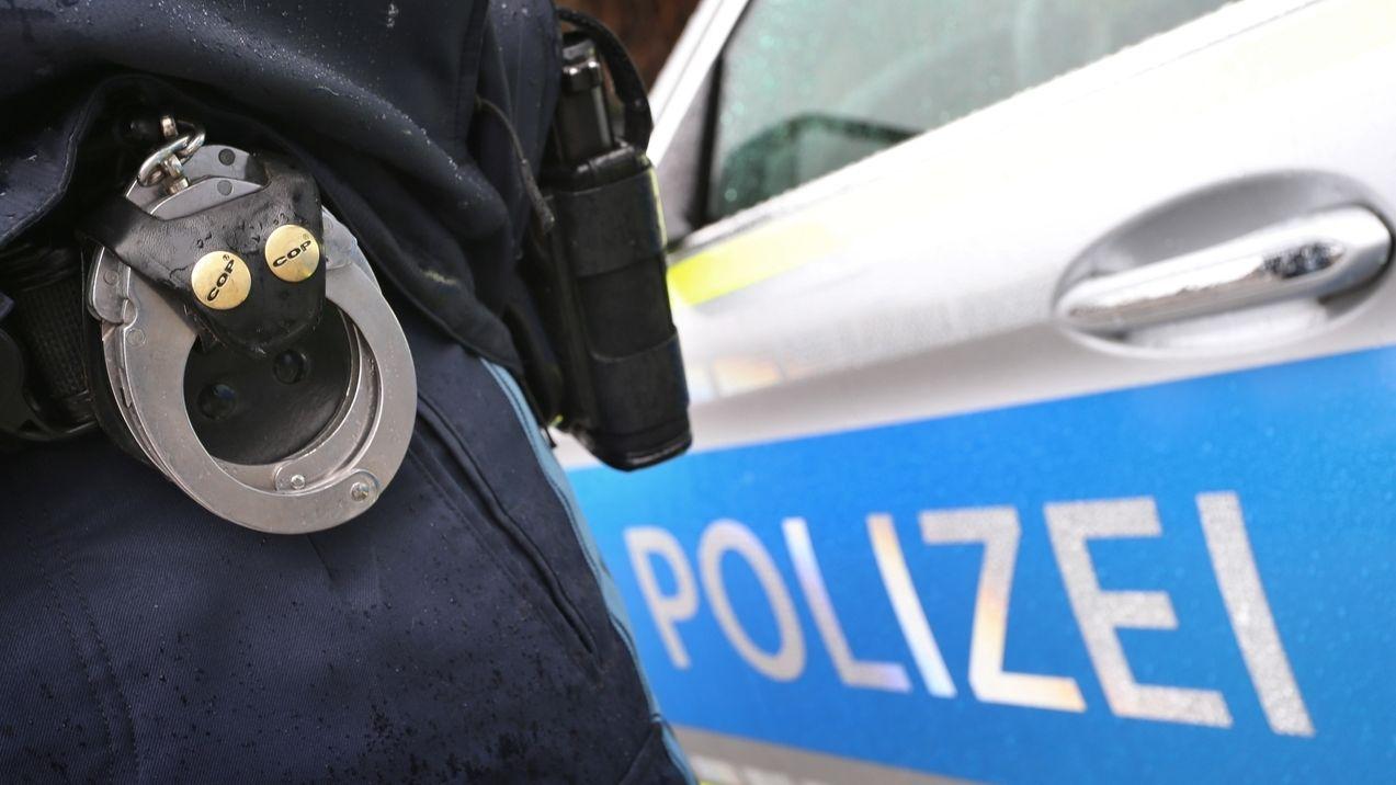 Ein Polizist mit Handschellen (Symbol)