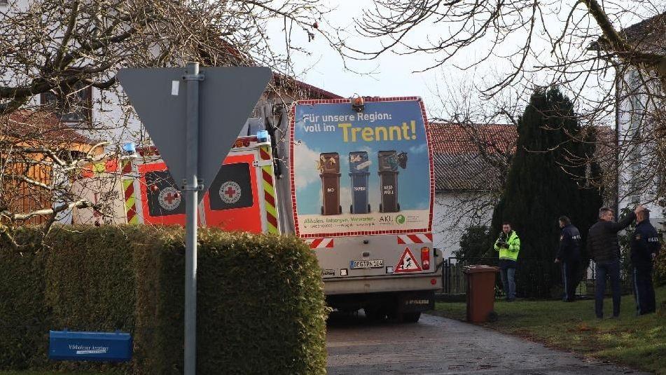 Ein Krankenwagen, das Müllfahrzeug und Polizisten an der Unfallstelle