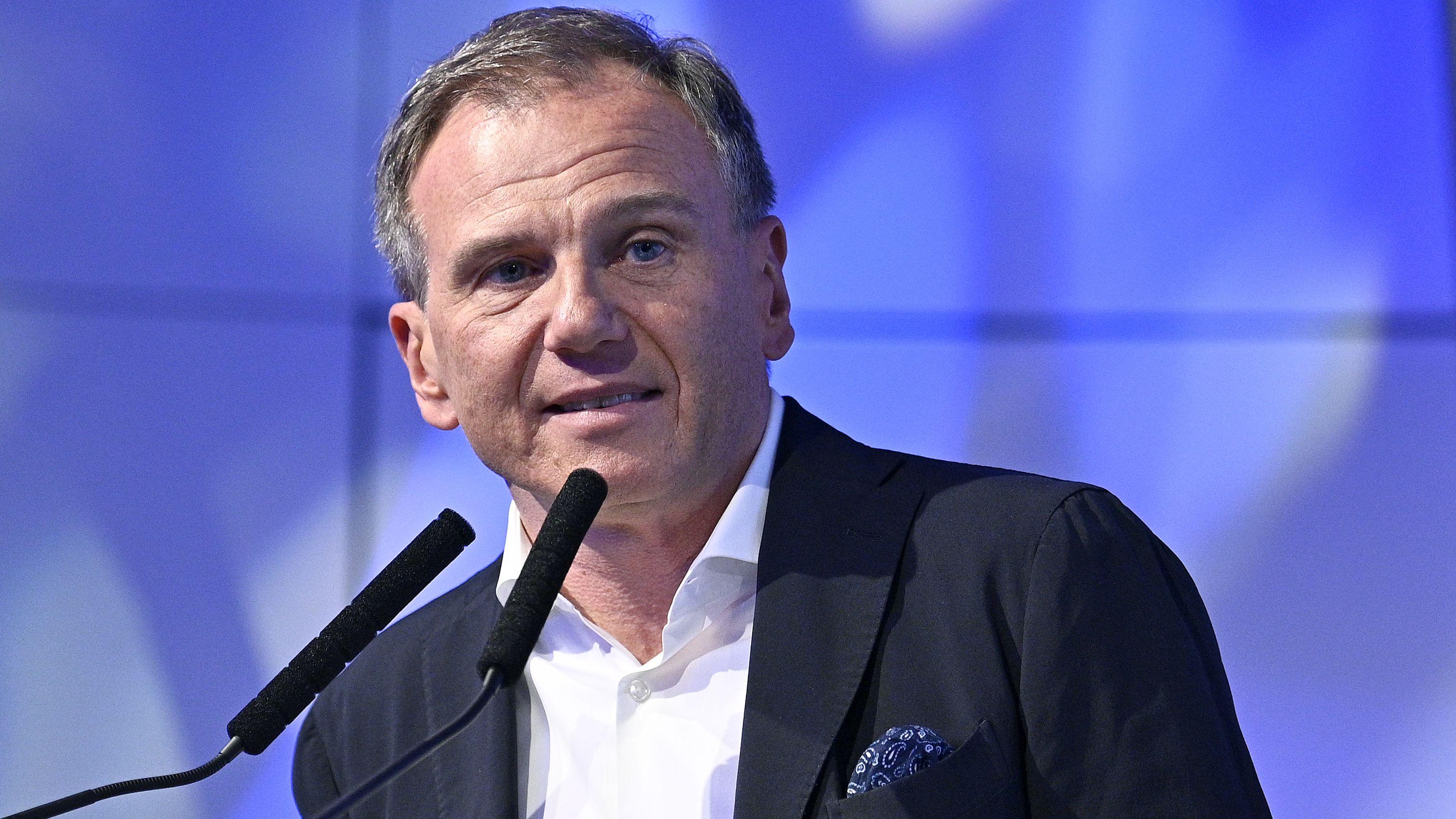 Armin Wolf steht hinter zwei Redner-Mikrofonen, er trägt ein weißes Hemd und ein schwarzes Jacket mit blauem Einstecktuch.