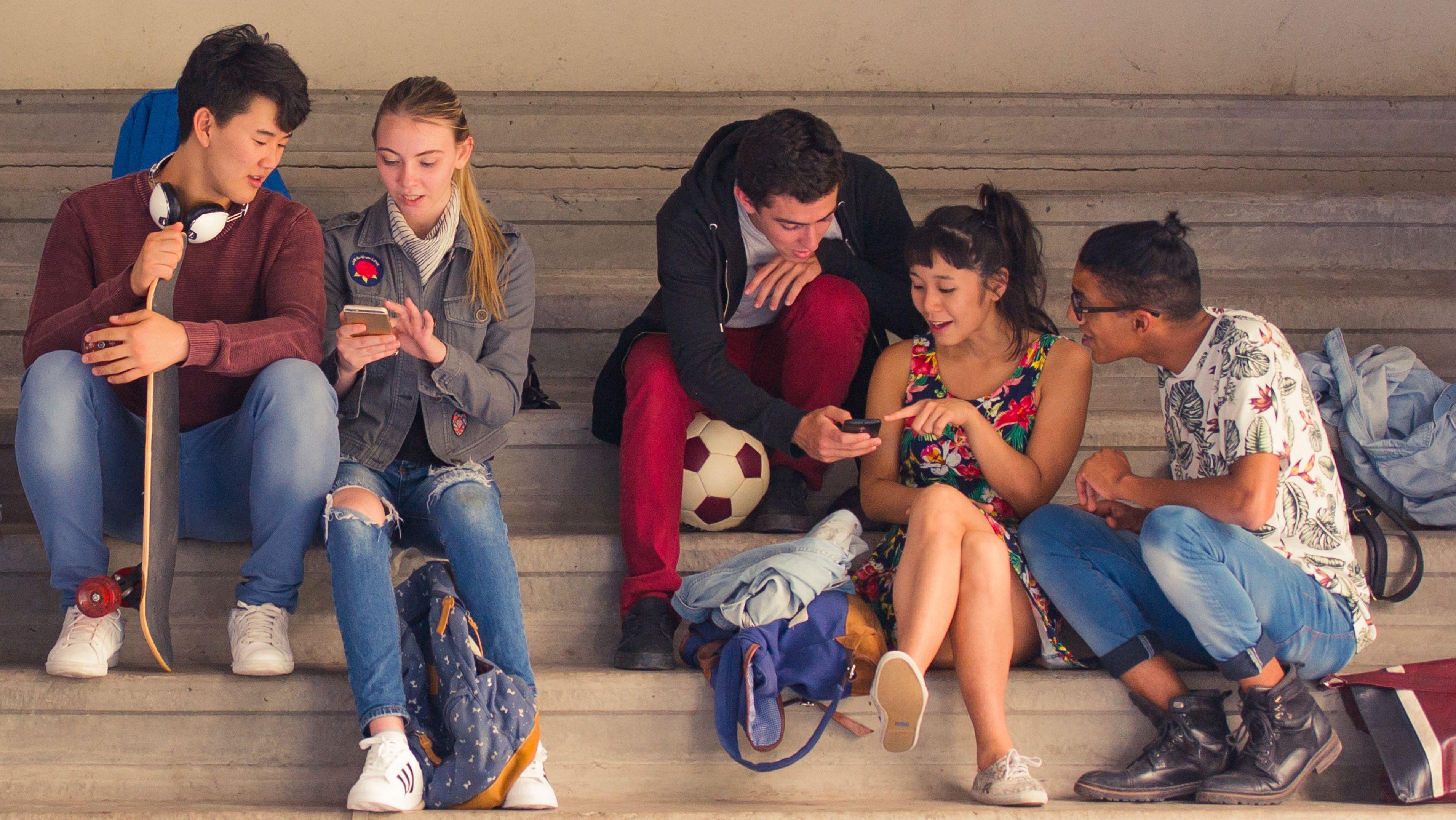 Jugendliche sitzen auf einer Treppe und schauen auf Smartphones.