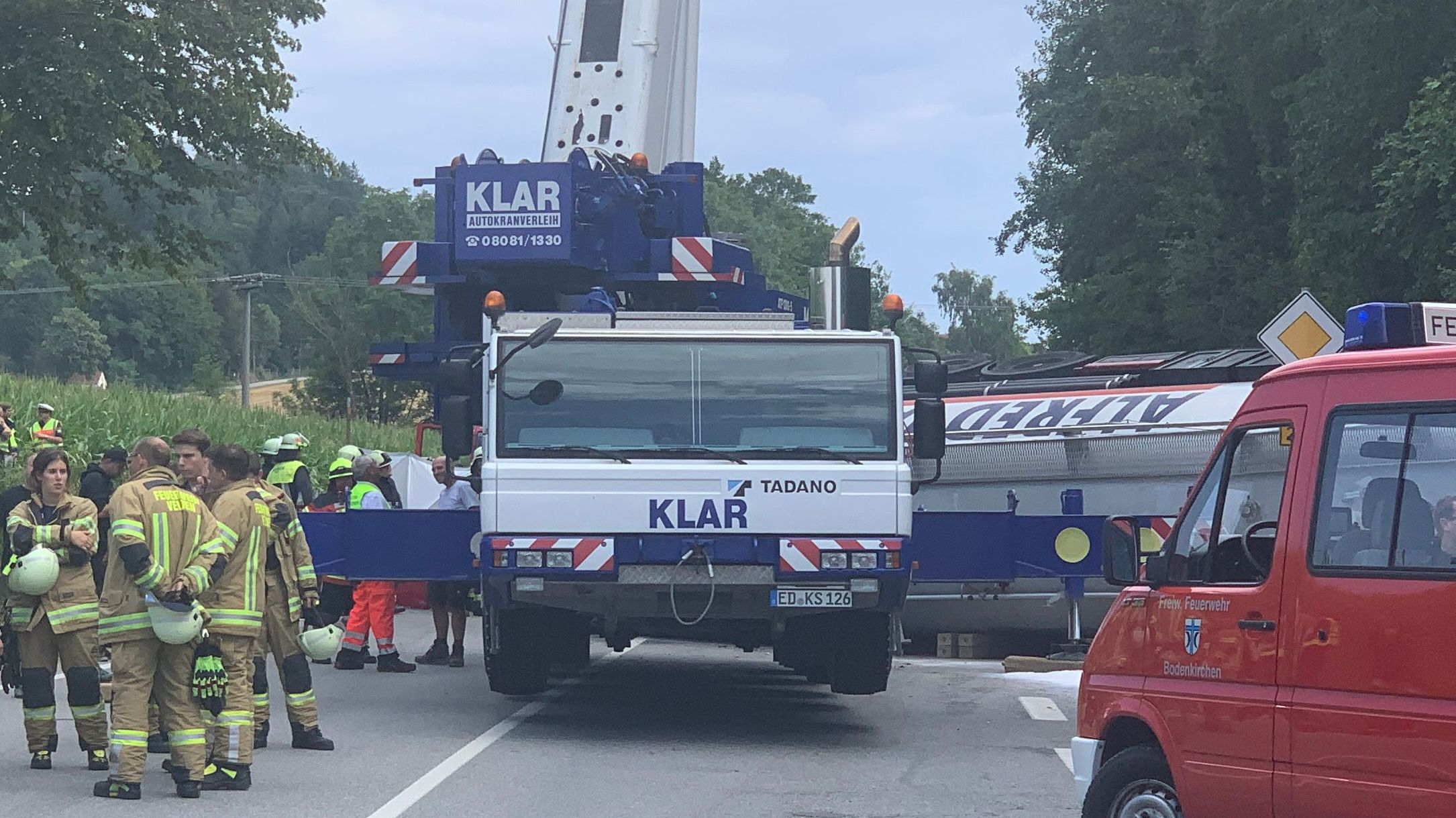Der Kran hob den umgekippten Laster an um an das Autowrack heranzukommen