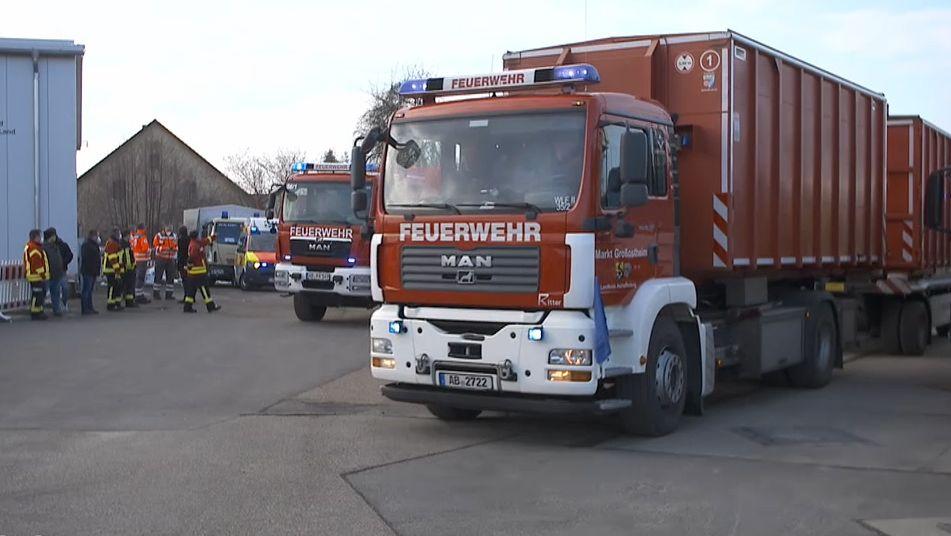 Feuerwehrautos stehen auf dem Parkplatz, daneben Feuerwehrleute in ihren Uniformen.