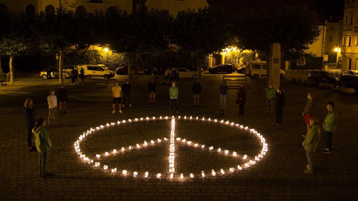 Die Organisation Greenpeace in Augsburg hat mit einem leuchtenden Peace-Zeichen aus Kerzen dem Atombombenabwurf über Hiroshima vor 75 Jahren gedacht.