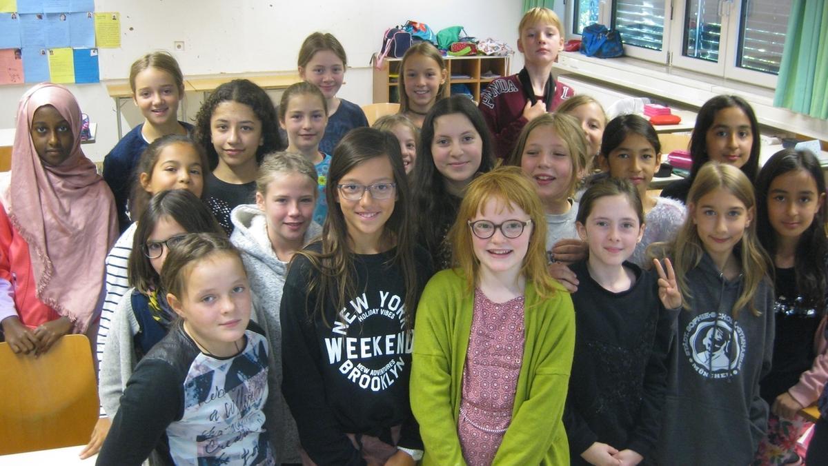 Blick ins Klassenzimmer der 5c am Sophie-Scholl-Gymnasium. Inmitten ihrer Mitschülerinnen stehen Anna und Nina, die frisch gewählten Klassensprecherinnen.