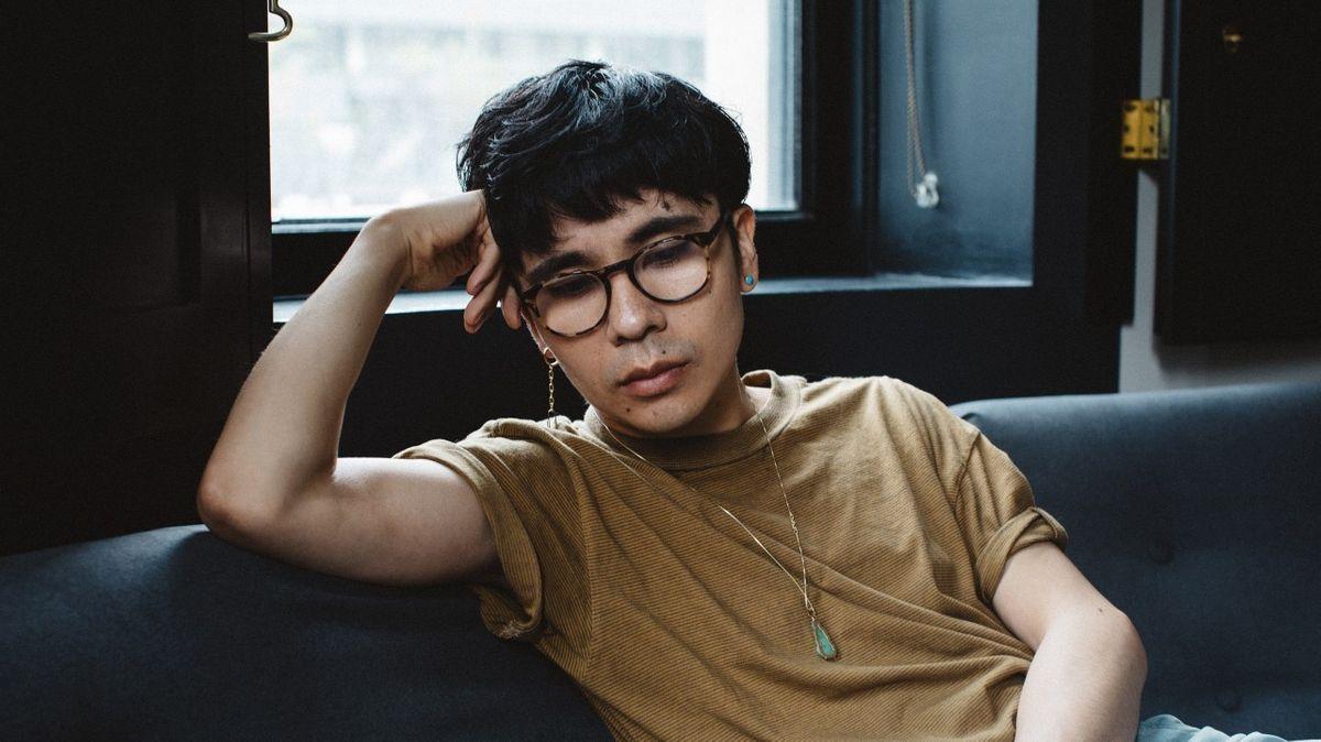 Der amerikanische Autor Ocean Vuong sitzt auf einem schwarzen Sofa und stützt den Kopf nachdenklich in die Hand.