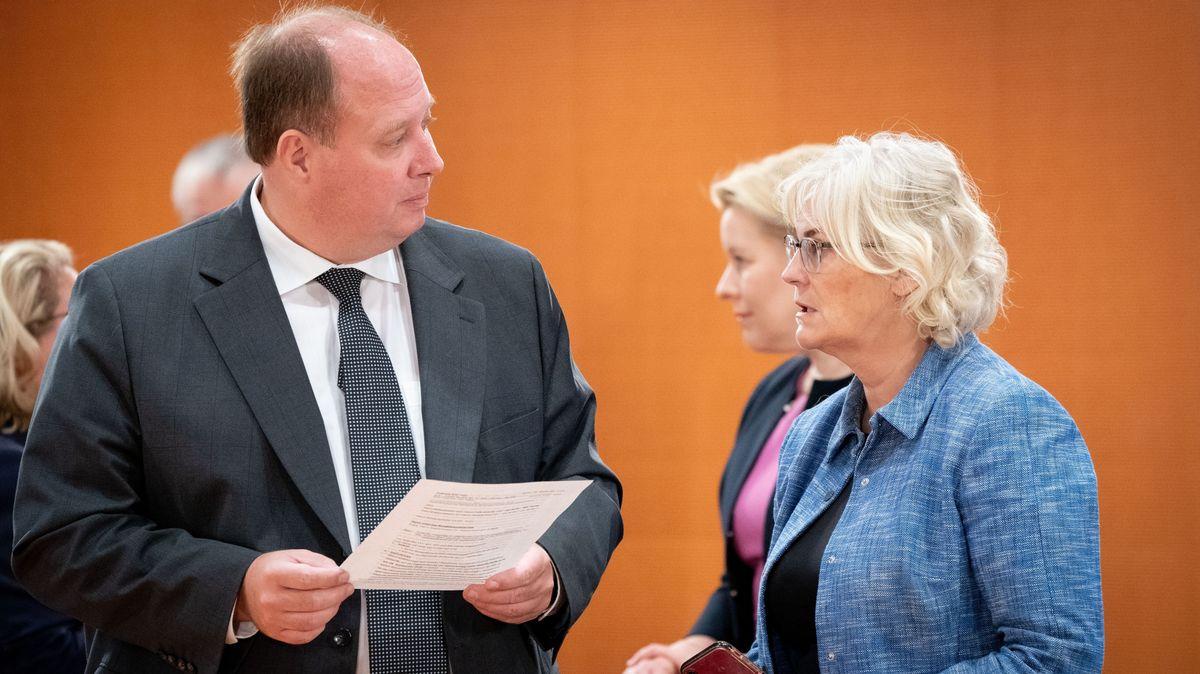Ein Mann und eine Frau blicken sich ernst an. Der Mann hält ein Papier in der Hand.