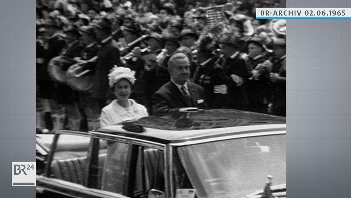 Königin Elisabeth II. im offenen Wagen stehend