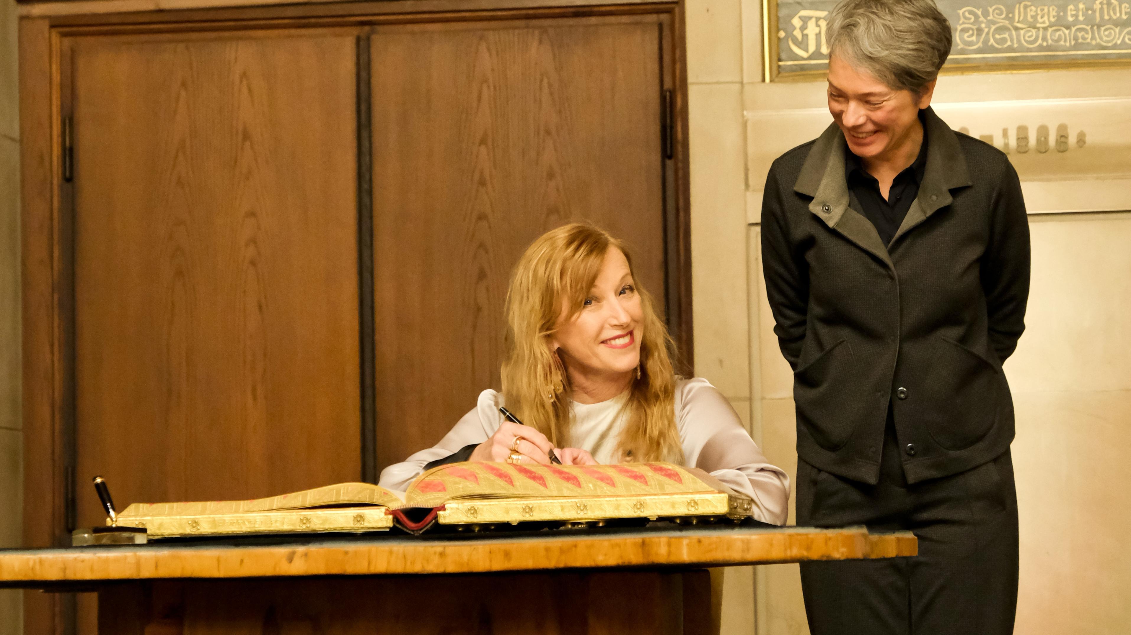Cindy Sherman trägt sich ins Goldene Buch der Stadt Frankfurt ein - beobachtet von Kulturdezernentin Ina Hartwig