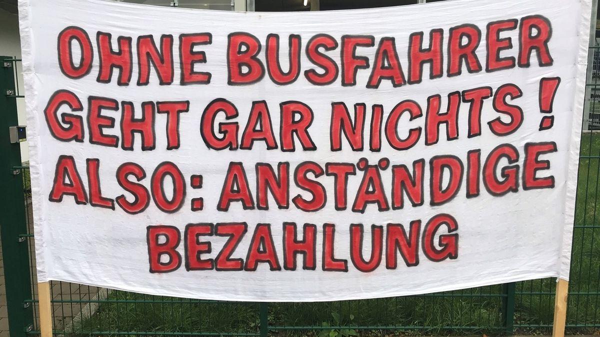 Auf einem weißen Transparent ist in roten Buchstaben zu lesen: Ohne Busfahrer geht gar nichts! Also: anständige Bezahlung.