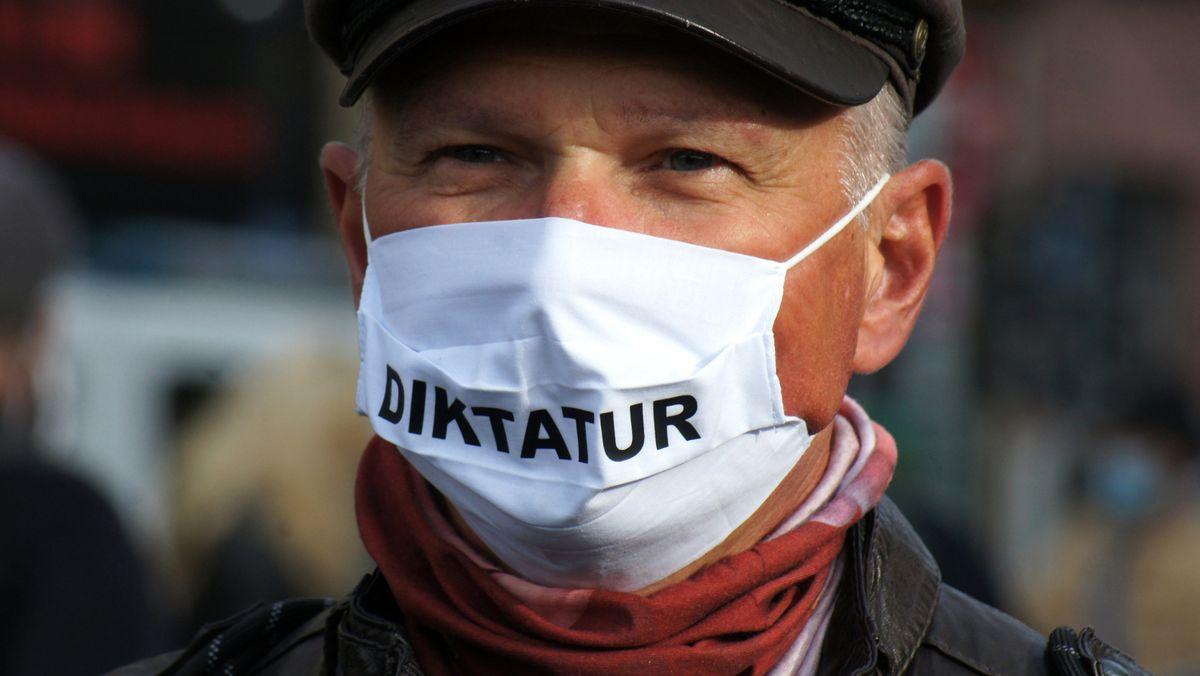 """Demonstration der """"Querdenker"""" in Frankfurt. Ein Teilnehmer glaubt wegen der Maskenpflicht als Corona-Schutz an die Einführung der Diktatur."""