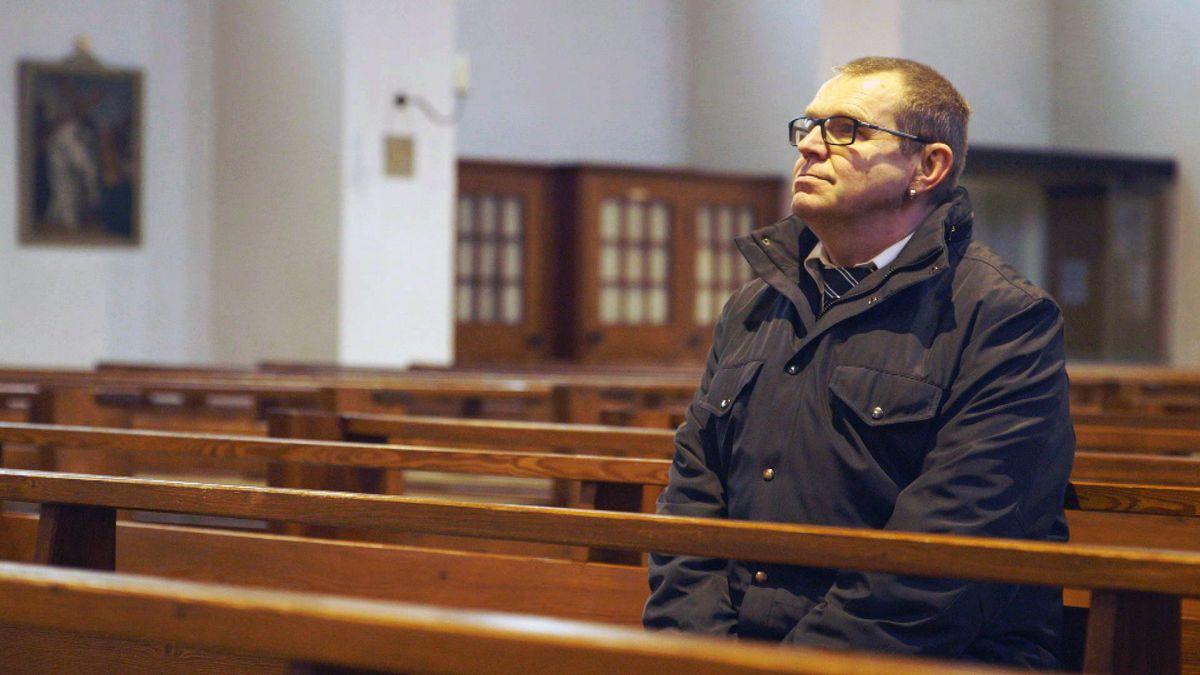 Johann Bannat im Kloster St. Ottilien: Er sitzt in einer Kirchenbank und blickt nach vorne.