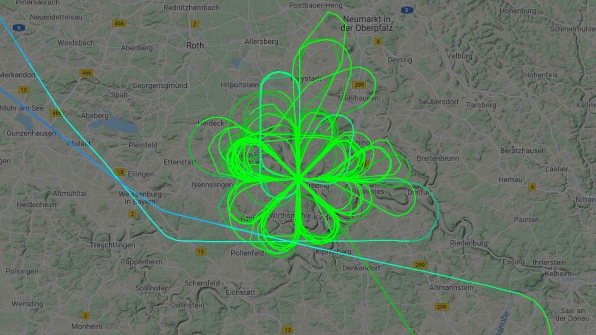 Eine grüne Linie über einer Landkarte zeichnet eine stilisierte Blume mit acht Blütenblättern.
