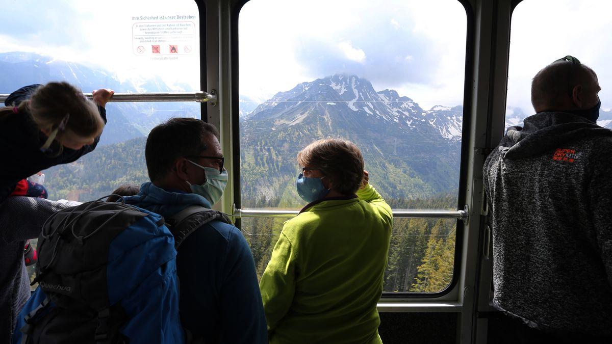 Ausflügler mit Mundschutz fahren in der Gondel der Fellhornbahn.