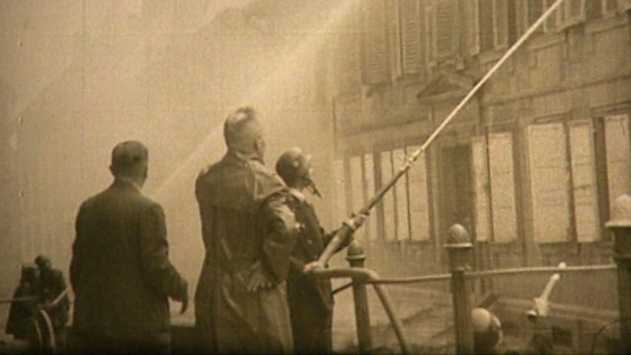Bild aus dem Zweiten Weltkrieg in Kronach: Feuerwehrmann löscht brennendes Gebäude.