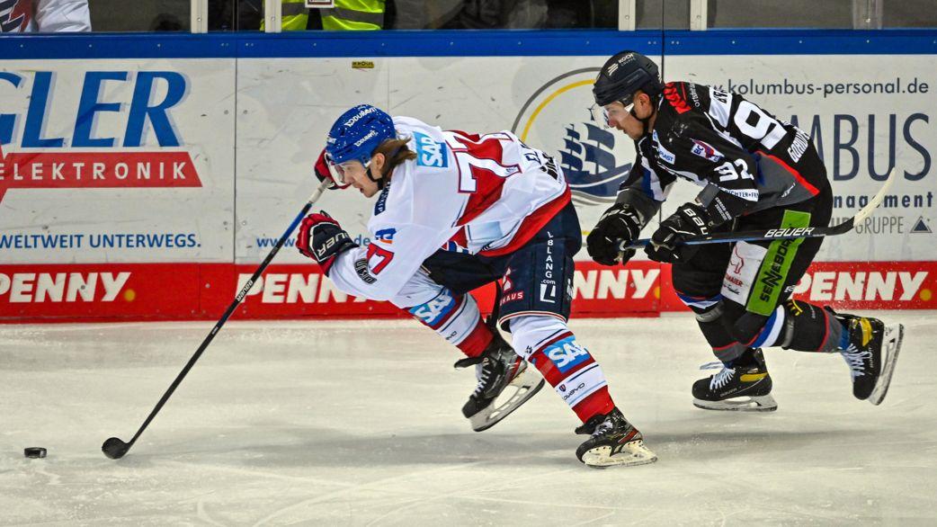Zwei Eishockeyspieler kämpfen um den Puck.
