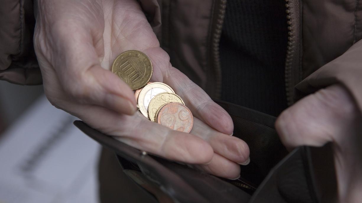 Eine alte Frau mit Kleingeld und einem Portmonee in den Händen