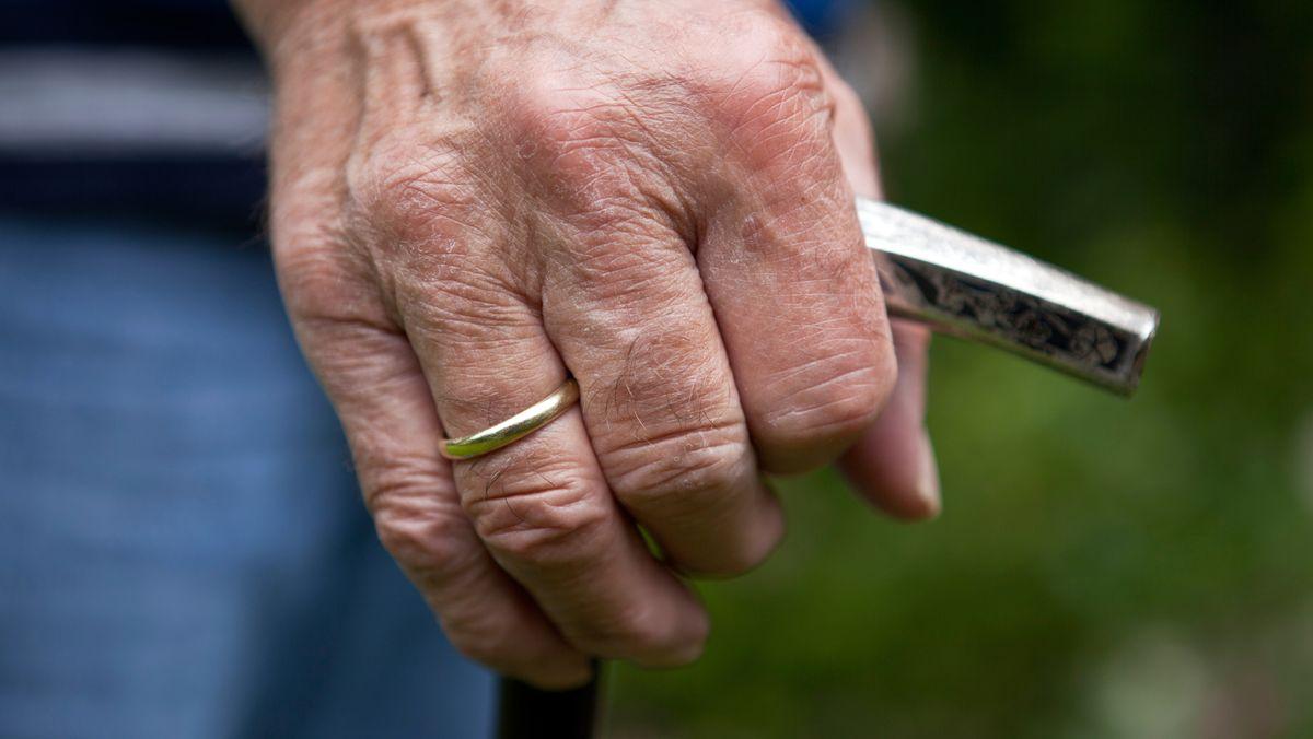 Symbolbild: Ein Mann mit Gehstock, die Hand umgreift den Knauf