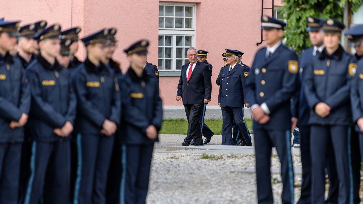 Polizistinnen und Polizisten stehen Spalier, im Hintergrund geht Innenminister Joachim Herrmann vorbei