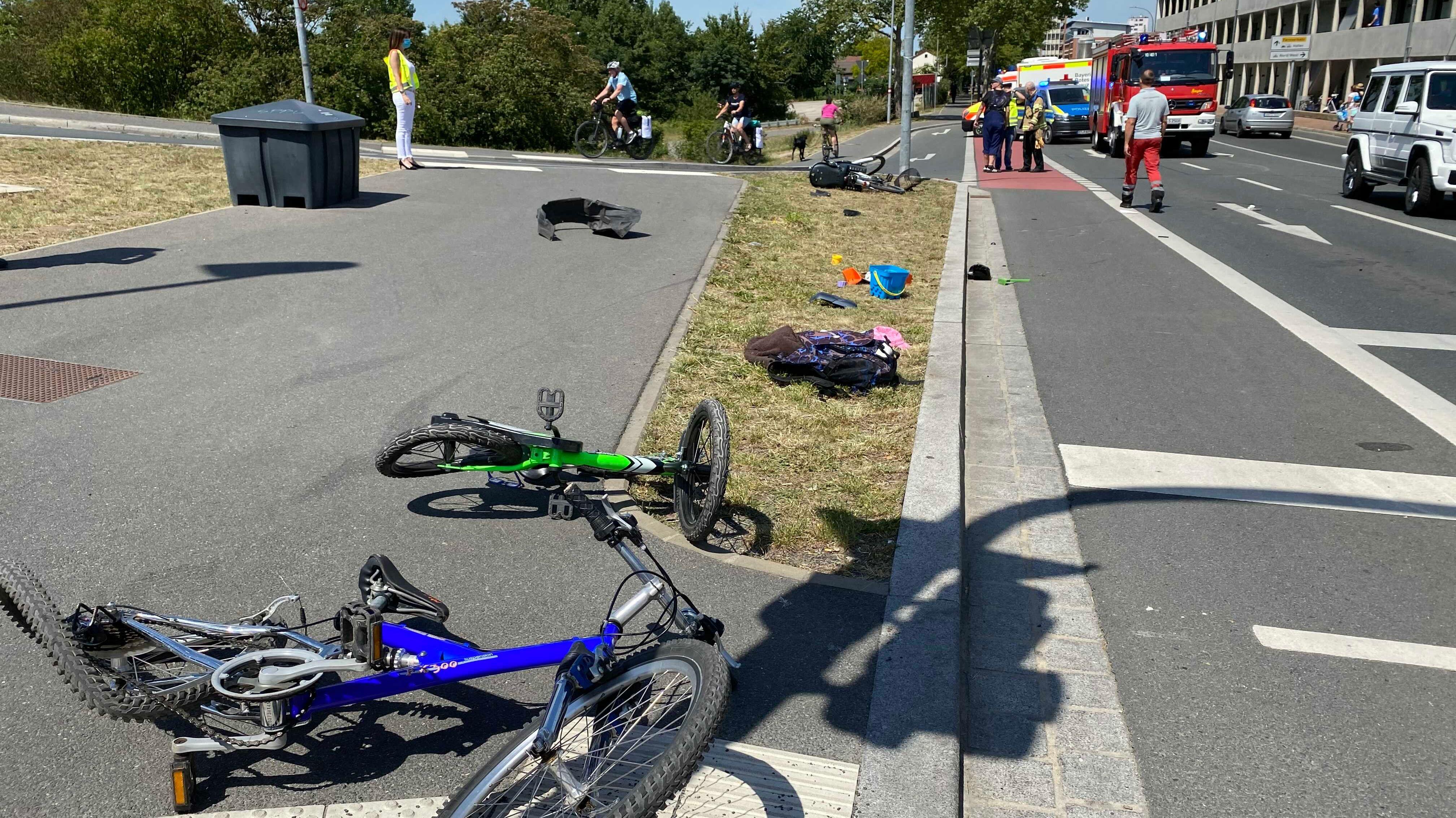 Zwei Fahrräder liegen an der Unfallstelle, dahinter steht ein Feuerwehrauto und ein Krankenwagen.
