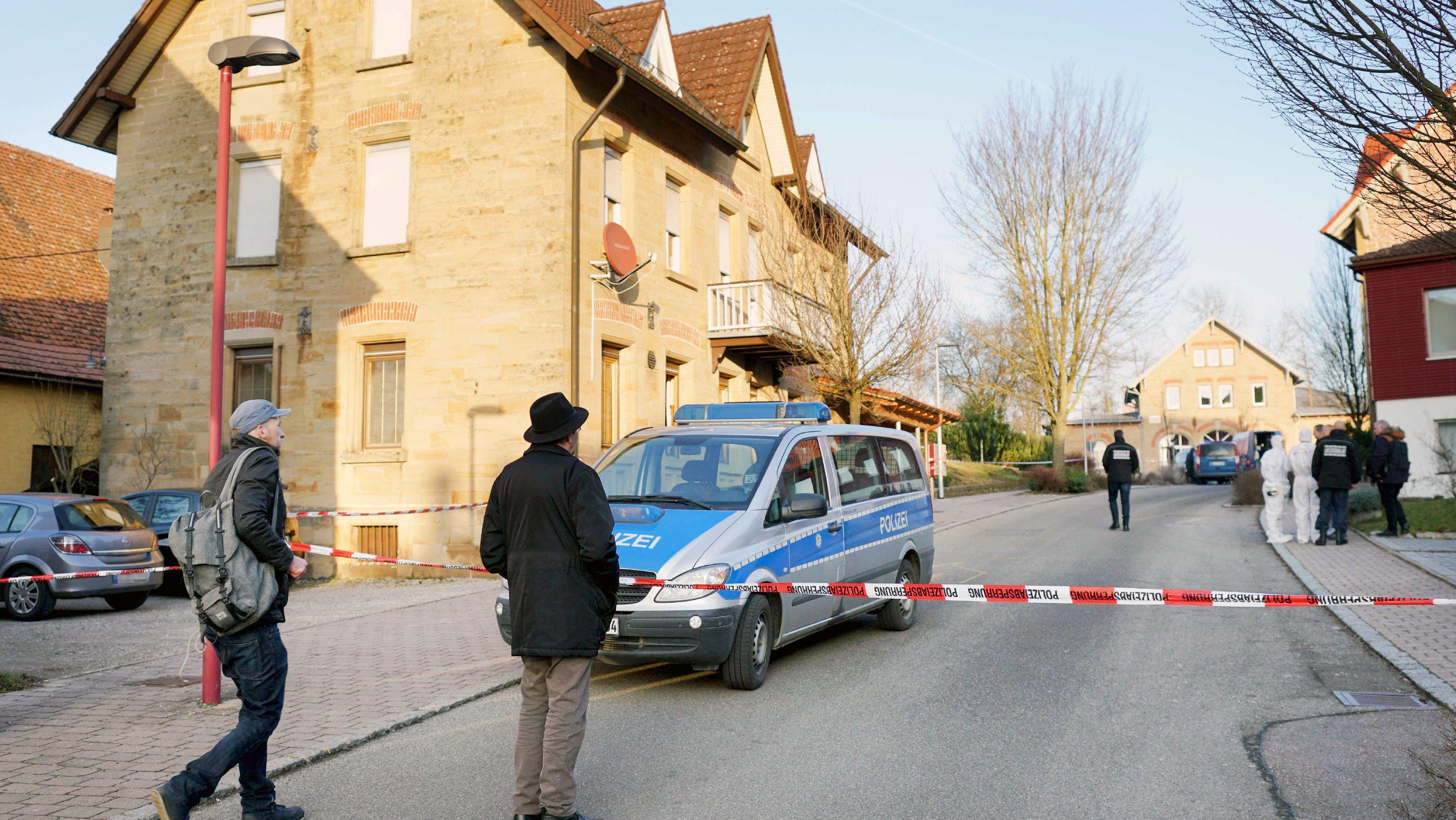 Nach Schüssen in Rot am See im Nordosten Baden-Württembergs stehen zwei Männer vor einer Polizeiabsperrung vor einem Haus. Hier sollen mehrere Menschen getötet worden sein.