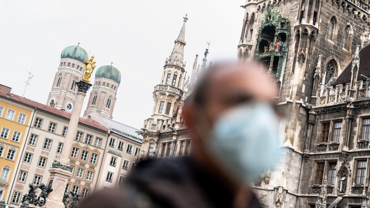 Ein Mann mit Maske am Münchner Marienplatz, im Hintergrund Rathaus und Frauenkirche