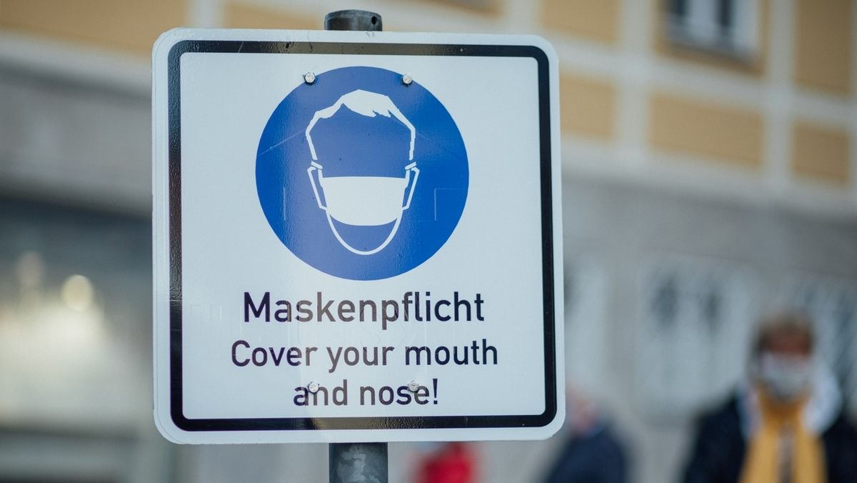 "Schild mit der Aufschrift: ""Maskenpflicht - Cover your mouth and nose!"""