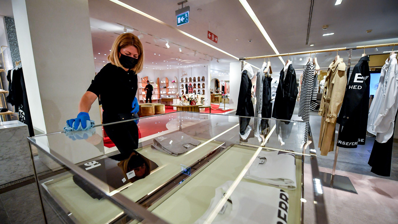 Eine Frau mit Mundschutz und Handschuhen reinigt eine Vitrine in einem leeren Bekleidungsgeschäft