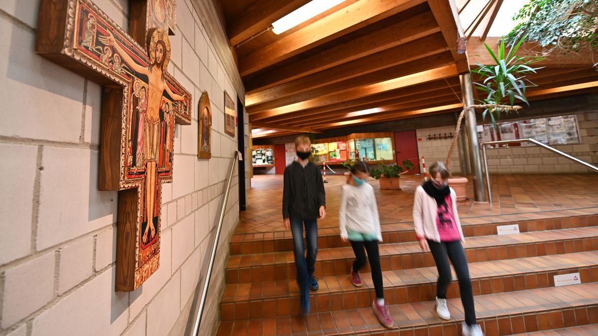 Drei Schüler gehen an einem Kreuz in einer Schule vorbei.