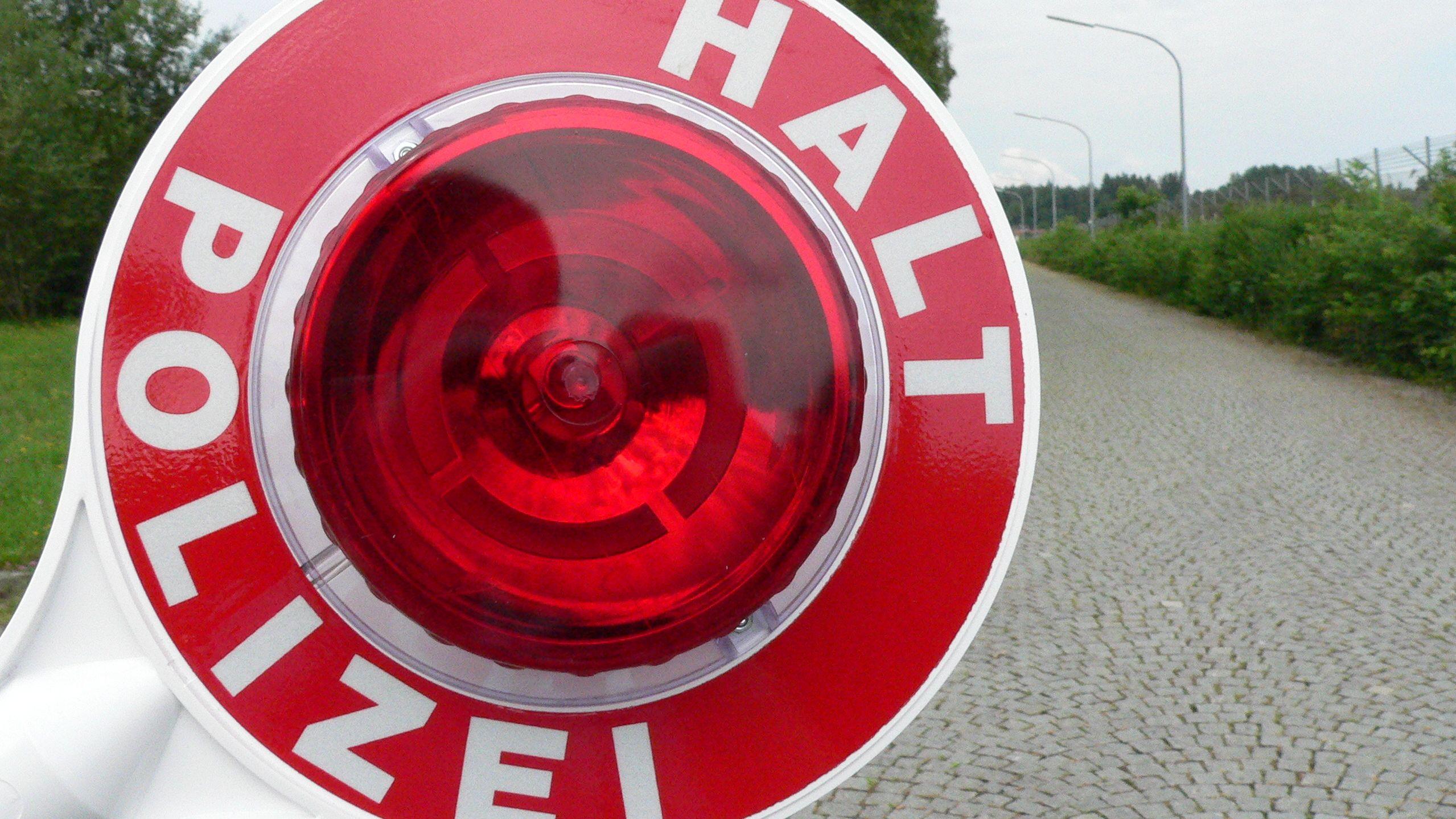 """Eine rote Polizeikelle auf der """"Halt"""" zu lesen ist."""