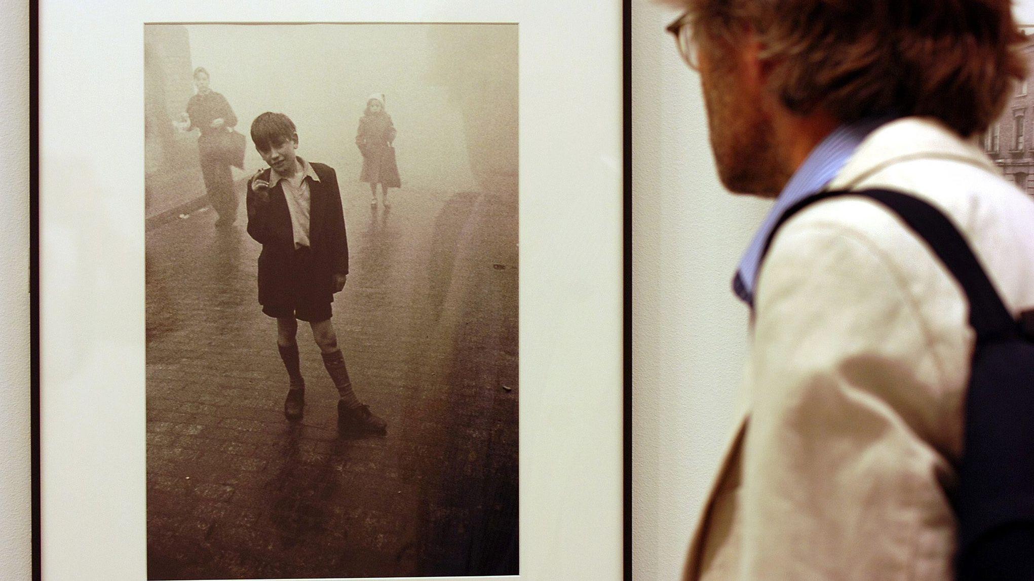 Ein Mann betrachtet im Fotomuseum Winterthur eine Fotografie Robert Franks: Zu sehen ist ein Straßenjunge, der frech in die Kamera blickt.
