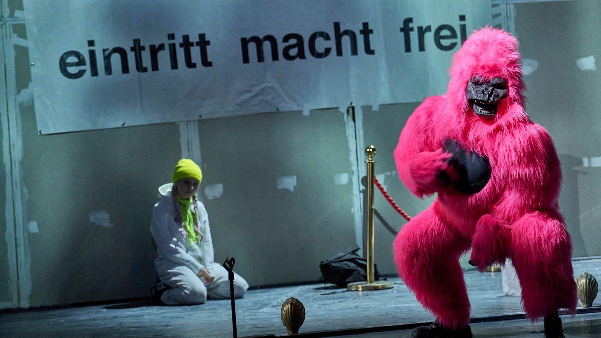"""Zwei Schauspieler auf der Bühne in Elfriede Jelineks """"Schwarzwasser"""", einer im rosa King-Kong-Affen-Kostüm"""